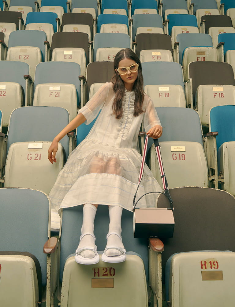 A model in velcro strap sandals, a top handle box bag and printed geometric frame sunglasses.