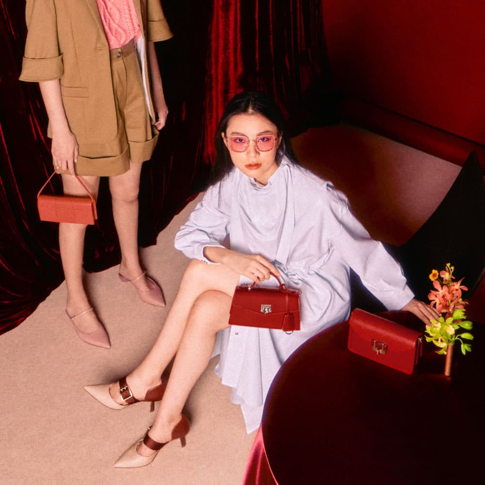 Women's brick oversized buckle pointed toe pumps, pink sculptural heel pointed toe mules, red trapeze top handle bag, coral panelled long wallet, red stone-embellished envelope bag and pink scallop trim butterfly sunglasses - CHARLES & KEITH