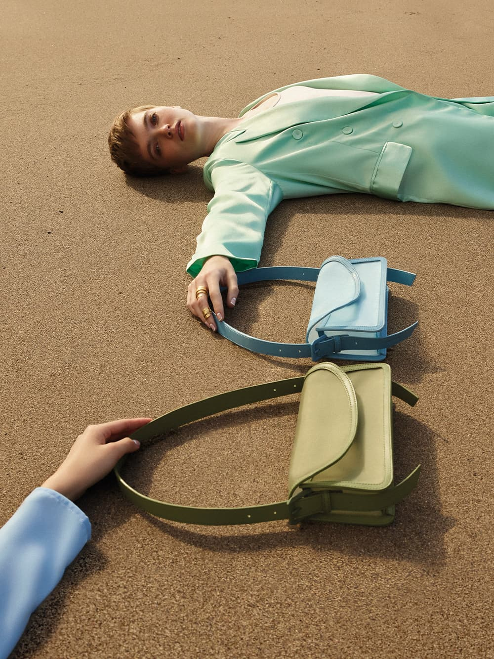 Models Ruth Bell and Zhao Jia Li strike poses in white mesh loafer mules, green and blue mesh shoulder bag, and brushed gold hammered double ring - CHARLES & KEITH