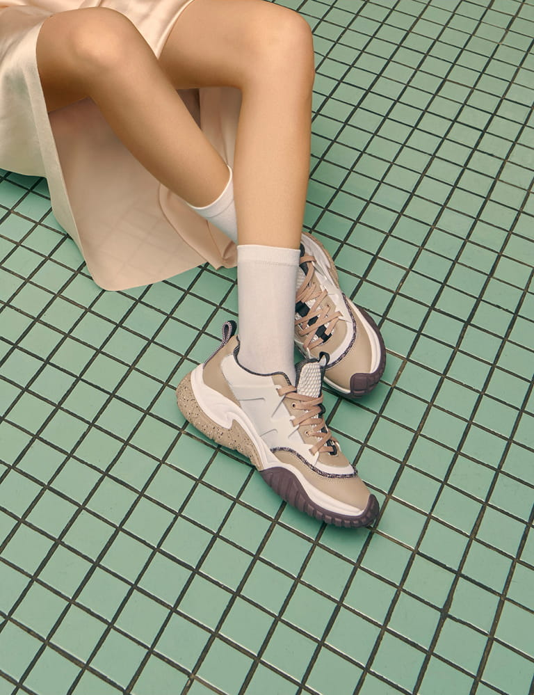 A pair of mesh chunky sneakers in nude pictured against green square tiles – sitting.